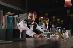 handsome bartender leaning on bar counter stock photography