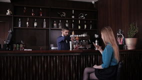 Handsome bartender making cocktails for beautiful women in a classy bar stock video
