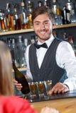 Handsome bartender making shots Royalty Free Stock Images