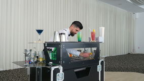 Handsome bartender mixing and preparing cocktail drink stock video footage