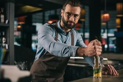 handsome bartender preparing alcohol drink and looking stock images