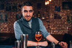 Handsome bartender preparing cocktail. Close up of bartender details with cocktails and bartending tools royalty free stock photography