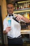 Handsome bartender serving blue cocktail Stock Images