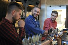 Handsome bartender is smiling and filling a glass with beer while standing at bar counter in pub stock images