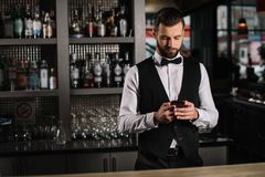 handsome bartender using smartphone stock photography