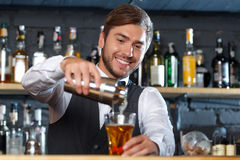 Handsome bartender during work. Portrait of a handsome bartender standing at the counter smiling and pouring a drink from a shaker to a glass, shelves full of Stock Photography