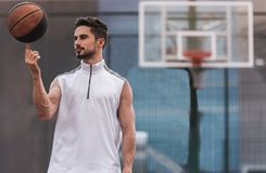 Handsome basketball player. Is spinning a ball on his finger while standing on basketball court outdoors Royalty Free Stock Photography