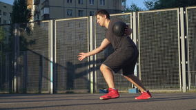 Handsome basketball player training outdoors. Adult caucasian man dribbling ball on the basketball court at the open air. Male trains sport skills in the morning stock video footage