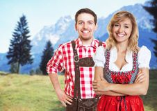 Handsome bavarian man and beautiful blonde woman with dirndl celebrating the oktoberfest stock images