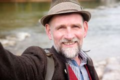 Bavarian man in his 50s standing by river and taking a selfie Stock Images