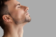 Handsome beard man. Side view of handsome young beard man keeping eyes closed while standing isolated on grey background stock photo