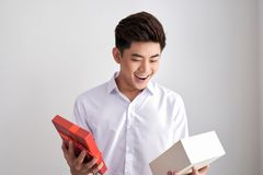 Handsome beard young man smiling and opening a brown gift box, g. Uy wearing white shirt, on white background stock photography