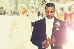 Handsome bearded african American groom touches wedding ring on finger. Handsome bearded men or african American groom in elegant suit coat with white tie and royalty free stock photo