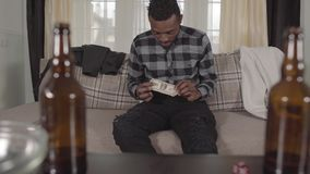 Handsome bearded african american man checking his pocket sitting on the sofa and finding one dollar only. Blurred empty stock video