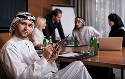 Handsome bearded Arab man working in the group Stock Photo
