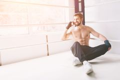 Handsome bearded boxer with bare torso is practicing at the fight club Stock Images