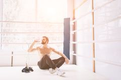 Handsome bearded boxer with bare torso is practicing at the fight club Royalty Free Stock Image