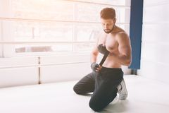 Handsome bearded boxer with bare torso wrapping his hands, ready to fight at the fight club. Stock Photo