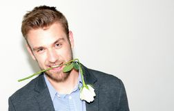 Handsome bearded boy smiling with white broken rose royalty free stock image