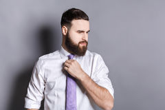 Handsome bearded businessman adjusting his tie Royalty Free Stock Photos