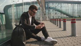 Handsome bearded businessman in the airport station typing text message on his mobile phone and sitting on the ground. Next to entrance stock video footage