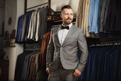 Handsome bearded businessman in classic suit. A young stylish man in a cloth jacket. It is in the showroom, trying on clothes, pos royalty free stock photography