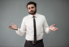 Handsome bearded businessman. In formal suit is lifting hands in dismay and looking at camera, on gray background stock photos
