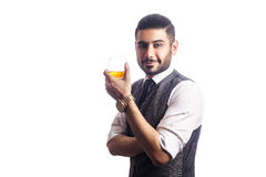 Handsome bearded businessman holding a glass of whiskey. Royalty Free Stock Images