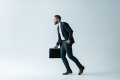 Handsome bearded businessman running with briefcase on grey Stock Photos