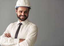Handsome bearded businessman. In suit and protective helmet is looking away and smiling while standing with crossed arms on gray background Royalty Free Stock Photos