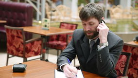 Handsome bearded businessman talking on the phone cheerfully during his coffee break on the cafe terrace stock video
