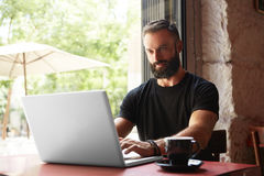 Handsome Bearded Businessman Wearing Black Tshirt Working Laptop Wood Table Urban Cafe.Young Manager Work Notebook Royalty Free Stock Photos