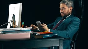 Handsome bearded businessman working on the computer and using his smartphone. Black background. 4K shot stock video footage