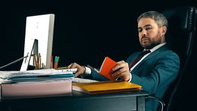 Handsome bearded businessman working on his computer and using his planner. Black background Stock Photos