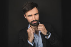 Handsome bearded confident businessman posing in black suit stock photo