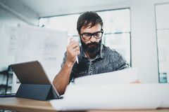 Handsome bearded designer working at the modern office loft.Coworker using electronic touch tablet computer on sunny. Workplace.Horizontal. Blurred background stock images