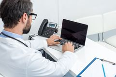 Handsome bearded doctor using laptop. At workplace Stock Photography