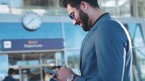 Handsome bearded Eastern businessman standing by the airport entrance, using his phone and smiles to received message. Texts back. Stylish suit, sunglasses stock video