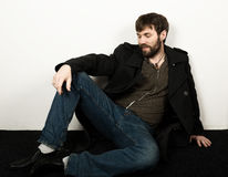 Handsome bearded elegant business man in a jacket, jeans and a woolen coat posing. feshion concept Stock Images