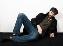 Handsome bearded elegant business man in a jacket, jeans and a woolen coat posing. feshion concept Royalty Free Stock Photography