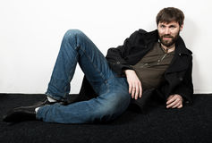 Handsome bearded elegant business man in a jacket, jeans and a woolen coat posing. feshion concept Stock Photo