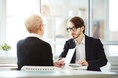 Conducting Negotiations with Business Partner. Handsome bearded entrepreneur sitting opposite his business partner while conducting negotiations at modern office Royalty Free Stock Photo