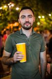 Handsome Bearded European Man Drinking coctail or beer at outdoor Street Cafe night party in park. Handsome Bearded European Man Drinking coctail or beer at Stock Photo