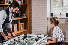 Handsome bearded father and little son playing. Table football Stock Image