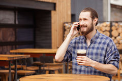 Handsome bearded guy is communicating on telephone Stock Photo