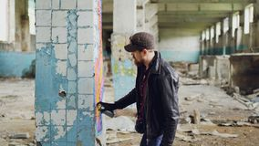 Handsome bearded guy is holding aerosol paint and drawing graffiti on pillar inside spacious abandoned house. Creative. Handsome bearded guy is holding aerosol stock video
