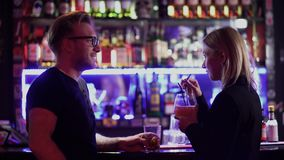 Handsome bearded guy and cute young woman with blond hair standing near a bar counter in a nightclub. A man and a girl stock footage