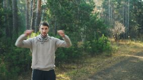 Handsome bearded guy is exercising outdoors in park warming-up arms and shoulders enjoying physical activity. Jogging. Handsome bearded guy in sportswear is stock video footage