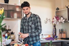 Handsome stylish guy preparing food in the kitchen at home. Handsome bearded guy with stylish haircut in casual clothes preparing food in the kitchen at home Royalty Free Stock Images