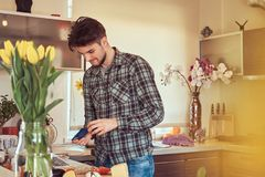 Handsome stylish guy preparing food in the kitchen at home. Handsome bearded guy with stylish haircut in casual clothes preparing food in the kitchen at home Stock Image
